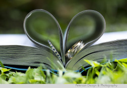Weddings rings tucked in book pages like a heart